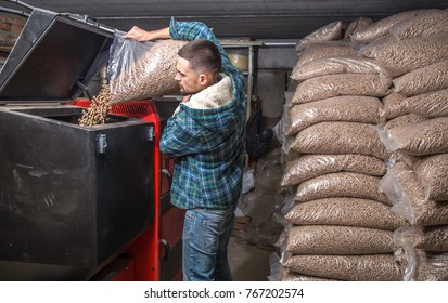 the man loads the pellets in the solid fuel boiler, working with biofuels, economical heating