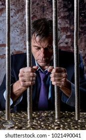 Man locked in a jail, whose bars are coins