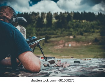 Man with a long barrel gun on shooting range