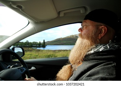 man with long beard,  drives in the car in highlands, highland of Scotland, near loch ness