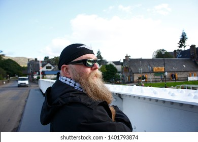 Man with long beard, glasses and headscarf, stands thoughtfully in the sluice gate in the Caledonian Canal