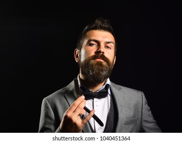 Man with long beard holds blade for razor. Macho in formal suit shaves beard. Business and barbershop service concept. Businessman with arrogant face isolated on black background.