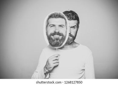 Man with long beard and mustache. Feeling and emotions. Guy or bearded man on grey background. Hipster with serious and happy face hold portrait nameplate. Barber fashion and beauty.
