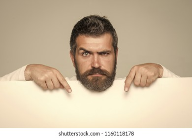 Man with long beard and mustache. Guy or bearded man on grey background. Feeling and emotions. Hipster with serious face hold paper. Barber fashion and beauty marketing.