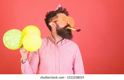 Man with long beard on red background. Bearded man in huge glasses with party whistle, celebration concept. Crazy man with trimmed beard having fun. Perfomer at kids event, International children day.