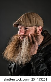 Man with long beard running his fingers through it.