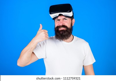 Man with long beard and serious face showing OK gesture. Hipster with trendy beard wearing VR goggles, digital technologies concept. Bearded brutal man testing 3D video isolated on blue background.