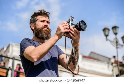 Man with long beard shooting photos. Manual settings. Photographer hold vintage camera. Modern blogger. Content creator. Man bearded hipster photographer. Photographer with beard and mustache.