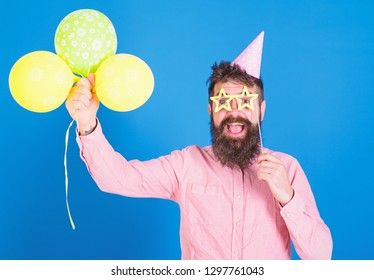 Man with long beard wearing birthday cap having fun with bright balloons. Art perfomer enterteining guests at children event. Bearded man with paper party accessories in pink shirt on blue background.