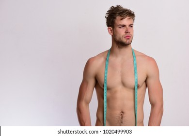 Man with long blue measuring tape around neck. Guy with proud face isolated on light grey background. Athlete with messy hair measures nude body. Measurement and sports lifestyle concept