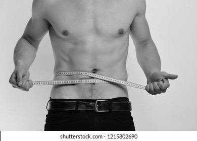 Man with long blue measuring tape around naked torso. Sports and weight loss concept. Athlete with strong muscles measures waist or sixpacks. Guy with nude chest isolated on white background