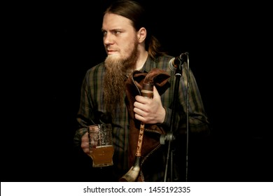 A man with long hair and a beard holds a bagpipe in one hand and a mug of beer in the other. Feast of beer. Beer day. Focus on hand with bagpipes