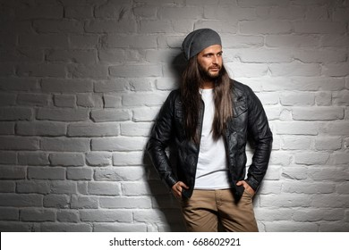 Man with long hair standing against wall, looking away. Copyspace.
