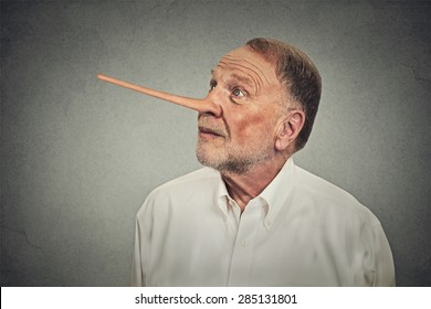 Man with long nose looking up avoiding eye contact isolated on grey wall background. Liar concept. Human face expressions, emotions, feelings.