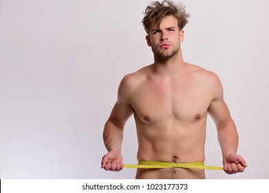 Man with long yellow tape measure around naked torso. Athlete with messy hair measures waist or sixpacks. Guy with serious face isolated on white background, copy space. Sports and weight loss concept