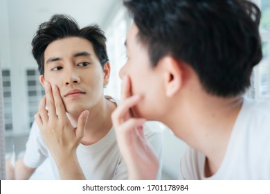 A man look at his face in the mirror and proud on his healthy skin.