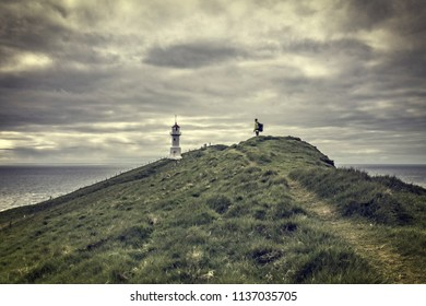 man look lighthouse in mykines faroe islands