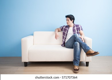 man look somewhere and sit on sofa at home
