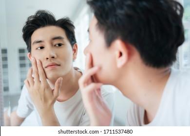 Ein Mann schaut auf sein Gesicht im Spiegel und stolz auf seine gesunde Haut.