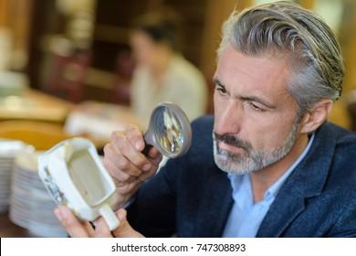 Man looking at antique jug through magnifying glass