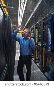 Man looking astonished in a network data center. Shot through a hexagonal door grille