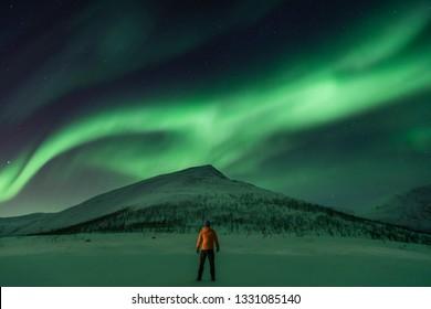 Man looking at the aurora (northern lights)