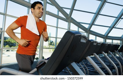 Man looking away while exercising on treadmill in gym