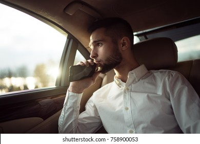 Man looking away while sitting on the back seat of a car, businessman in taxi
