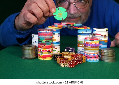 Man looking from behind a stack of casino chips, slot tokens and dice on green felt surface. Placing $1000 chip on top. PDK
