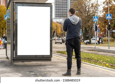 The man looking at the blank billboard for advertisement isolated on white background at a public transport stop.
