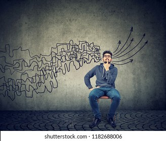 man looking up brainstorming getting his thoughts together planning making conclusions isolated on gray wall background