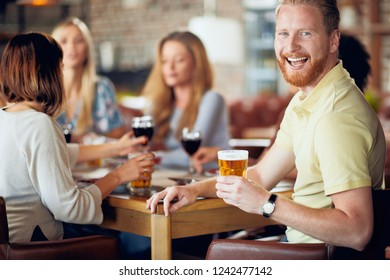 Man looking at camera and drinking beer while sitting in restaurant. In background friends chatting.