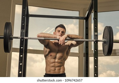 Man looking at camera. Handsome man face. Sportsman, athlete with muscles looks attractive. Sport and gym concept. Man with torso, muscular macho lean on barbell, window on background. Man with nude