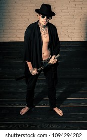 Man looking at camera. Man with sword standing on wooden floor barefoot, top view. Warrior in black hat and open clothes showing tattooed torso. Honor and dignity. Samurai, buddhist concept. Handsome