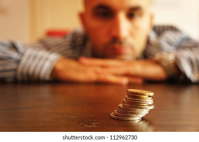 Man looking at coins and thinks