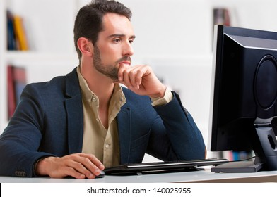 Man looking at a computer screen, thinking about the job at hand