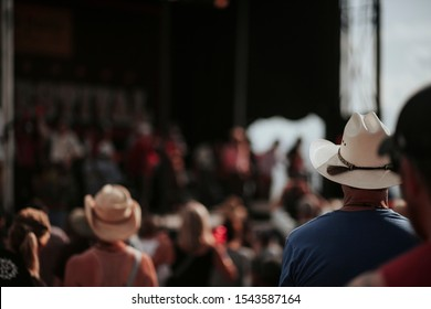 Man looking with crowd onto stage of music venue