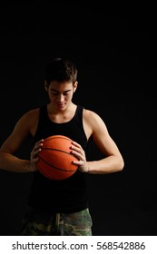 Man looking down at basketball in hands