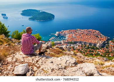 man looking down to the Old Town of Dubrovnik, enjoying beautiful view, sitting on the mountain above the city