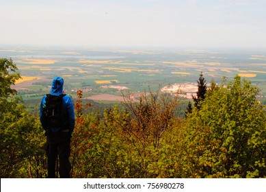 Man looking down on the view under peak. Hiking in the mountains, person with backpack on a trip. Trees, fields, meadows, cities, villages and sky, aerial view from the top. Sport relaxing weekend.