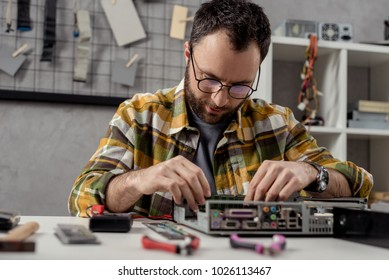 man looking down while fixing broken computer