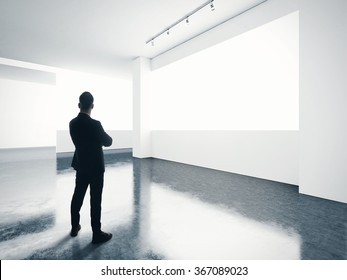 Man looking at empty screen in contemporary gallery.