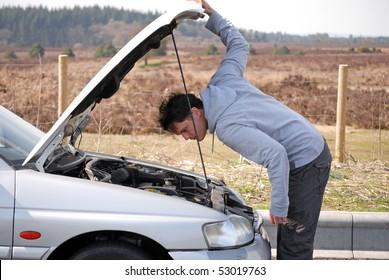 Man looking at engine of car