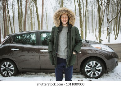 Man looking excited standing in front of his newly bought car in winter forest road. Auto business. Winter car service