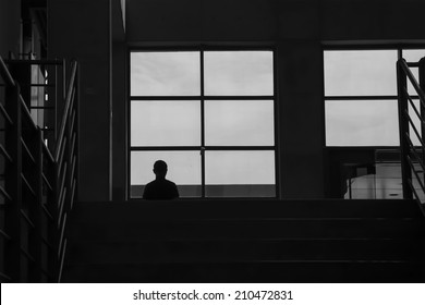 a man looking forward in front of the window