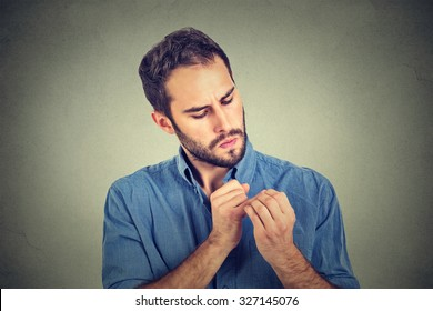 man looking at hands nails obsessing about cleanliness germs isolated on gray background. Negative human emotion facial expression, feeling, life perception