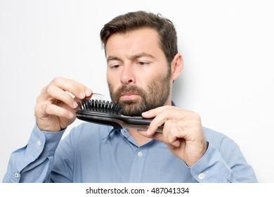 man looking at his hairbrush