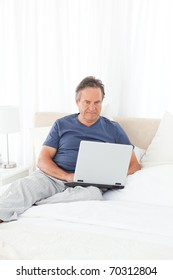 Man looking at his laptop on his bed