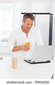 Man looking at his laptop while he is drinking oranje juice