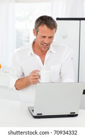 Man looking at his laptop while he is drinking at home